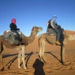 My husband and I riding camels in the sahara